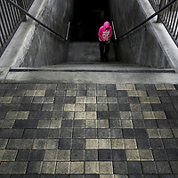woman wearing pink stands in a grungy stairwell of contrasting grays.  taken at the los angeles metro, union station, southern california, usa.