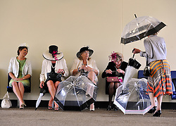 © licensed to London News Pictures. ASCOT, UK.  16/06/11. Ladies shelter from the rain. People arrive at Royal Ascot during a torrential downpour of rain.  Ladies Day at Royal Ascot 16 June 2011. Royal Ascot has established itself as a national institution and the centrepiece of the British social calendar as well as being a stage for the best racehorses in the world. Mandatory Credit Stephen Simpson/LNP
