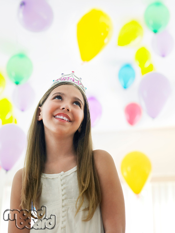 Girl (10-12) in tiara smiling looking up at balloons
