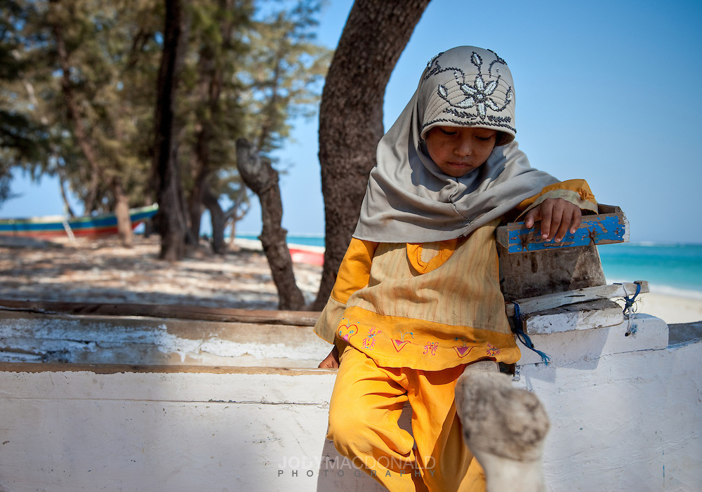 A young shy muslim girl sits on a fishing canoe near a white sand beach offshore Sumba, Indonesia.  A small fishing community sails from Lombok every season and sets up a temporary simple and meager camp.  The men fish, the women collect seaweed and the children assist or play.
