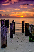 The sun sets on the Gulf of Mexico behind the Old Pilings on Naples Beach,