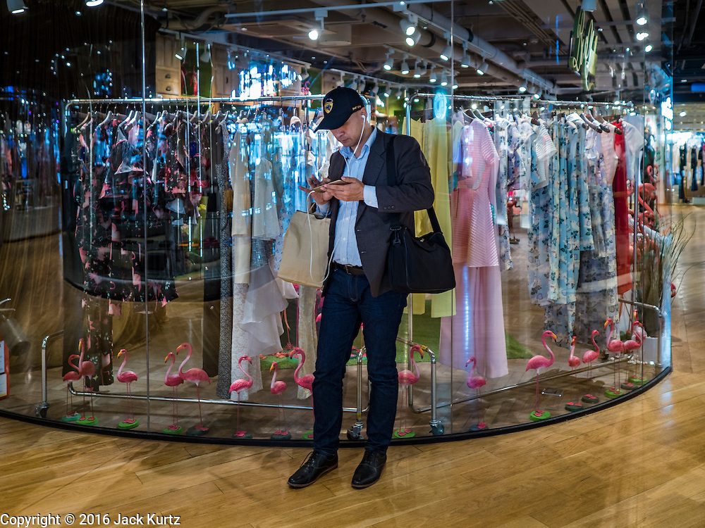 12 FEBRUARY 2016 - BANGKOK, THAILAND: A man uses his smart phone in Siam Center, one of the trendiest malls in Bangkok. It's in the middle of Bangkok's exclusive retail area.           PHOTO BY JACK KURTZ