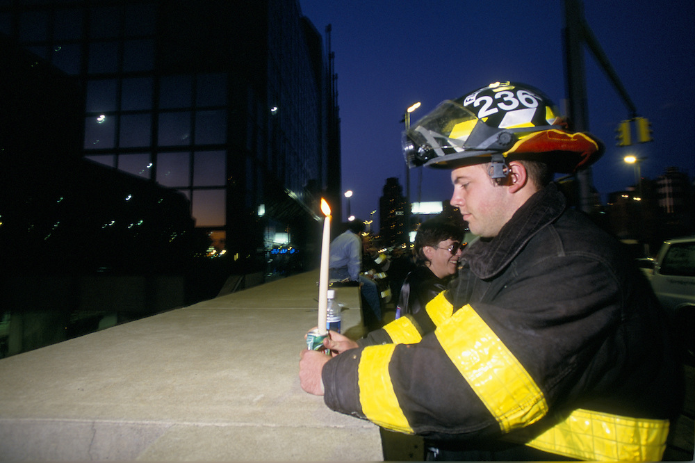 Kentucky firefighter places candle at memorial service at the Jacob Javits Center for the victims of the terrorist attack on the Twin Towers in NYC on 9/11/2001.