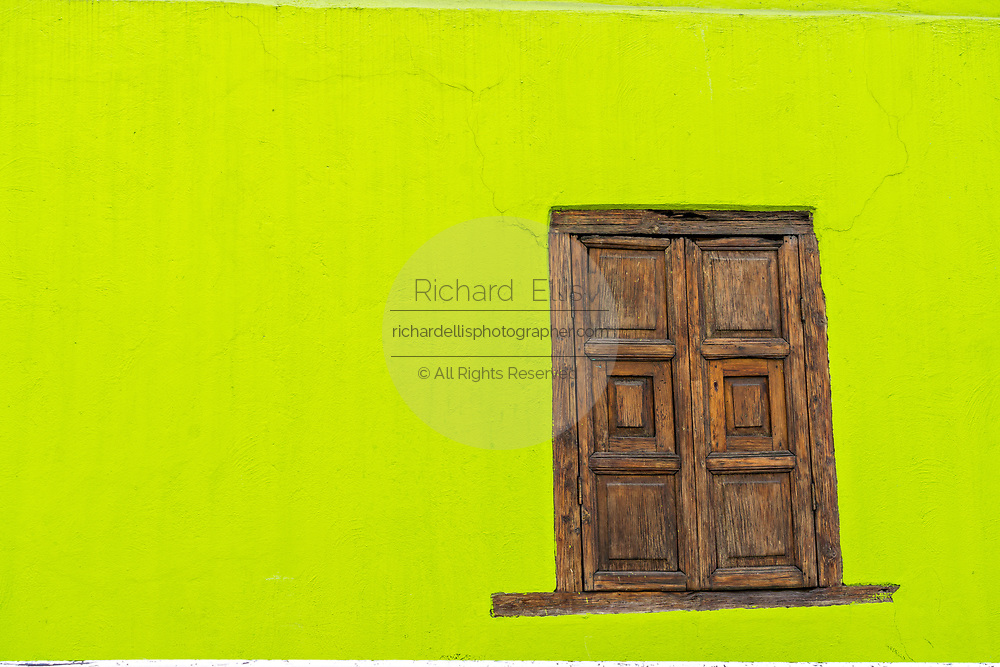 A lime green wall and wooden shutters in Angangueo, Michoacan, Mexico. Angangueo is a tiny, remote mountain town and the entry point to the Sierra Chincua Monarch Butterfly Sanctuary.