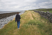 Model released young boy walking along coastal path, west coast of Ireland, County Clare, near Ballyvaughan