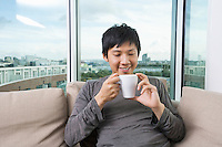 Mid adult man holding coffee cup in house