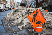 A bright orange road work sign warning people of traffic road works in front of a large pile of snow on East Houston Street in Lower East Side, New York City, New York, Unites States of America.  In January 2016 the city experienced a record breaking snowstorm.  (photo by Andrew Aitchison / In pictures via Getty Images)