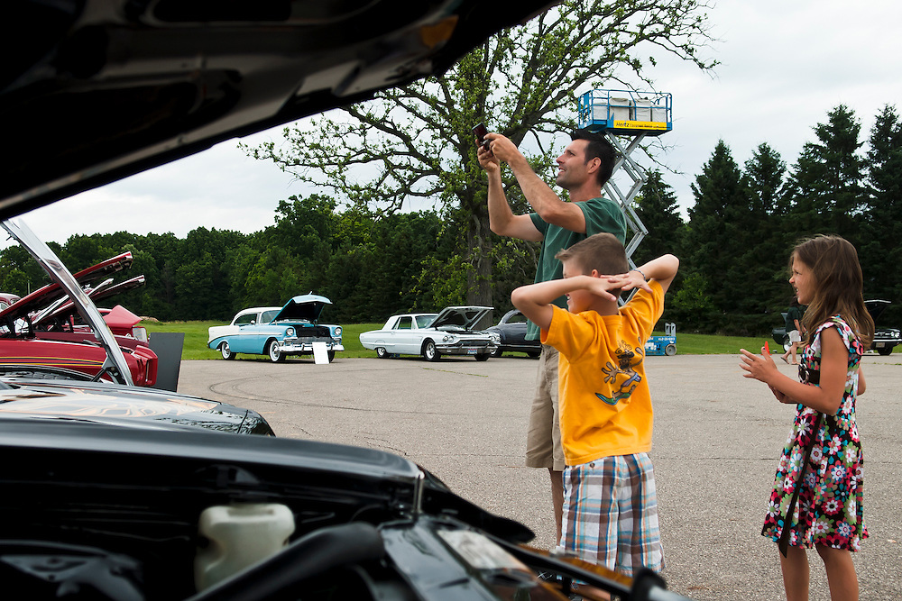 Lathan Goumas | MLive.com..Oscar Elizando, of Corunna, takes a picture of the hood of a car as he stands with his children Karson and Kailey, both 8, during the Shriner's 9th Annual Classic Car Show in Clio on Sunday.