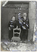 severely eroding glass plate with elderly couple posing in front of door