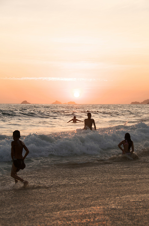Playing in the waves at sunset. Ipanema Beach, Rio de Janiero, Brazil.