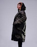 Studio portrait of a black female in a green hooded coat