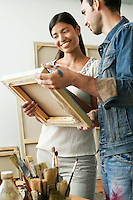 Couple looking at canvases in artist studio