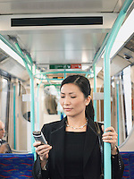 Businesswoman Using Cell Phone holding onto bar on Train