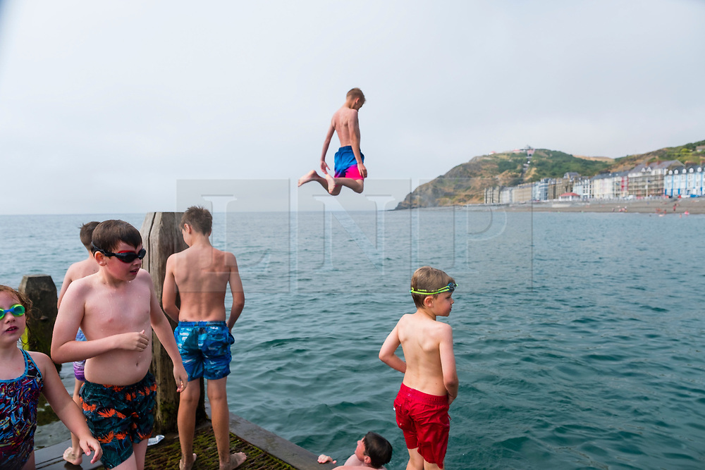 © Licensed to London News Pictures. 07/07/2018. Aberystwyth, UK. Teenagers jumping and diving into the sea of the jetty in Aberystwyth to cool down on yet another scorchingly hot and cloudless day, as the prolonged heatwave continues to dominate the weather over the UK. Photo credit: Keith Morris/LNP