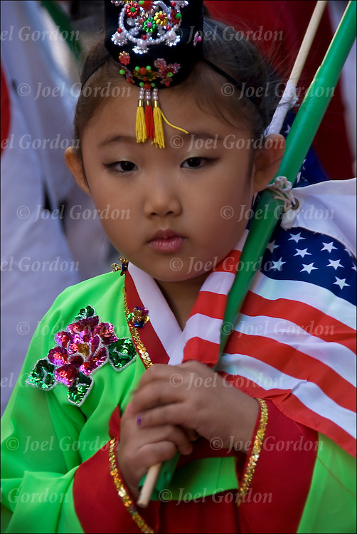 Young Korean American girl showing her Korean pride in the 30th Annual Korean Harvest Parade in New York City. She is  wearing traditional folk regalia / costume when celebrating the harvest and holding both American and Korean flags.