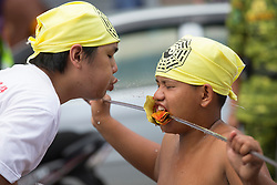 © Licensed to London News Pictures. 28/09/2014. Ipoh, Malaysia. A helper sprays water onto a devotee with a rod pierce through his mouth as devotees process with deities through the streets of central Ipoh, Malaysia on the 5th day of the Nine Emperor Gods Festival, Sunday, Sept. 28, 2014. The festival is a nine-day Taoist celebration to mark the birth of the Nine Emperor Gods from the first day to the ninth day of the ninth moon in Chinese Lunar Calender. The origin of the Nine Emperor Gods (stars of the Northern constellation) can be traced back to the Taoist worship of the Northern constellation during Qin and Han Dynasty and absorb this practice of worshipping the stars and began to deitify them as Gods. Photo credit : Sang Tan/LNP