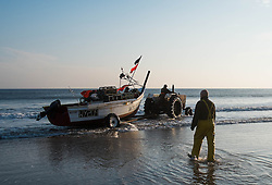 © Licensed to London News Pictures. <br /> 24/04/2015. <br /> <br /> Saltburn, United Kingdom<br /> <br /> Lesley Jefferson walks through the shallows as his brother, Malcolm Jefferson launches his boat, Ellen, as they head out to lay his lobster pots. Malcolm runs the last remaining commercial fishing boat out of Saltburn.<br /> <br /> <br /> Photo credit : Ian Forsyth/LNP
