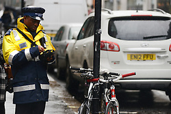© Licensed to London News Pictures.17/01/2014. London, UK A traffic warden is checking cars on Wardour Street in Soho, London. Wardour Street is the most ticketed road in the country, according to figures obtained under the Freedom of Information Act. Between January and October last year 5,143 tickets were issued, raising up to £410,000..Photo credit : Peter Kollanyi/LNP