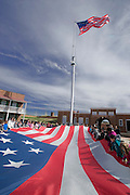 "Photo by Phil Grout..Fifth grarde students at Baltimore Highlands Elementary School help roll up the ""Garrison Flag"" as the ""Storm Flag"" flies above the students at the historic fort during a recent field trip."