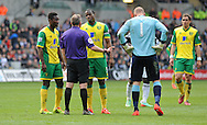 Referee Jonathan Moss has words with Norwich City Captain Sebastien Bassong.<br /> Barclays premier league match , Swansea city v Norwich city at the Liberty stadium in Swansea, South Wales on Saturday 29th March 2014.<br /> pic by Phil Rees, Andrew Orchard sports photography.