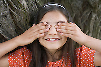 Girl (7-9) playing hide and seek covering eyes by tree