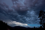 Stormy sky at twilight over forested mountains. Magenta color is from nearby lightning bolt. © 2014 David A. Ponton