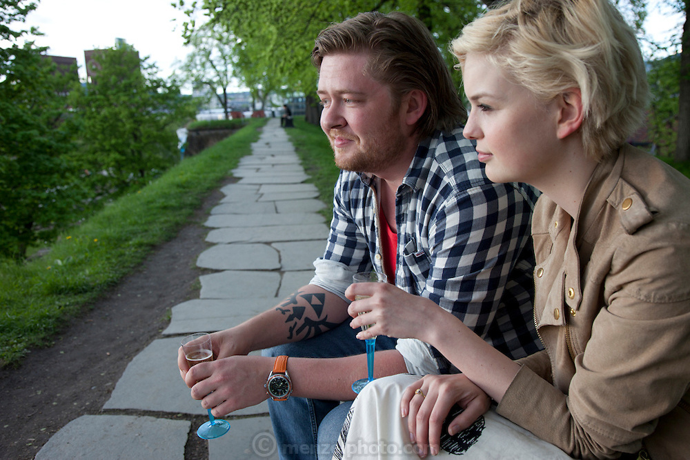 Couple enjoying champagne in a park overlooking the harbor in Oslo, Norway.