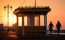 © Licensed to London News Pictures. 14/09/2016. Portsmouth, UK.  People strolling along the promenade as the sun rises over South Parade Pier in Southsea this morning, 14th September 2016. Temperatures are set to remain warm over the coming days in the south of England. Photo credit: Rob Arnold/LNP