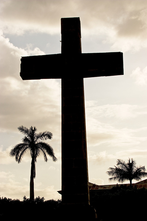 A cross stands out in the late day surrounded by palm trees in the Nicaraguan town of Granada