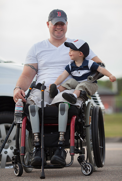 Injured Air Force Master Sgt. Joseph Deslauriers Jr., smiles as his 17 month old son Cameron sits in his lap, during a visit home to Bellingham, MA on Monday, May 20, 2013. In 2011, Deslauriers lost both of his legs and part of an arm after stepping on an explosive device while stationed in Afghanistan. He is currently rehabbing at Walter Reed Army Medical Center.  (Matthew Cavanaugh for The Washington Post)