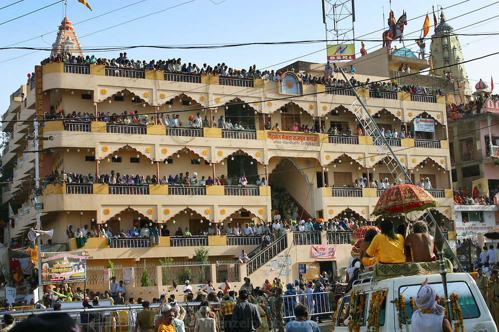 Watching a parade from a hotel by the Shipra River during Kumbh Mela in Ujjain, India. The Kumbh Mela festival is a sacred Hindu pilgrimage held 4 times every 12 years, cycling between the cities of Allahabad, Nasik, Ujjain and Hardiwar. Participants of the Mela gather to cleanse themselves spiritually by bathing in the waters of India's sacred rivers. Kumbh Mela is one of the largest religious festivals on earth, attracting millions from all over India and the world. Past Melas have attracted up to 70 million visitors.