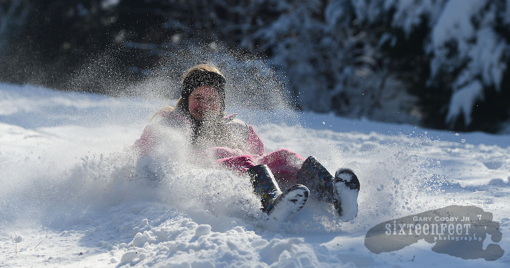 Gary Cosby Jr./Decatur Daily   Snow blankets the Tennessee Valley Thursday morning after a snow that began late Wednesday and fell through much of the night.  A spray of snow covers Devyn Owens as she sleds down a big hill on Colony Lane in Hartselle.