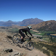 Jed Rooney from Oamaru in action during the New Zealand South Island Downhill Cup Mountain Bike series held on The Remarkables face with a stunning backdrop of the Wakatipu Basin. 150 riders took part in the two day event. Queenstown, Otago, New Zealand. 9th January 2012. Photo Tim Clayton