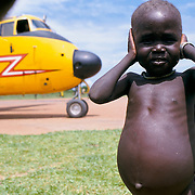 'SOUTH SUDAN, AUGUST 1998', FAMINE: MALNOURISHED CHILD SHIELDS  HIS EARS FROM THE NOISE OF A BUFFALO PLANE DELIVERING FOOD AID, 1998