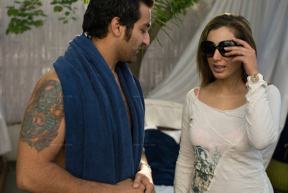 A young Indian guy with a tatoo of the Indian God Shiva on his arm chatting wiht a  fashionable Indian girl on a sunday afternoon at the Aqua pool club of the Park Hotel in New Delhi.