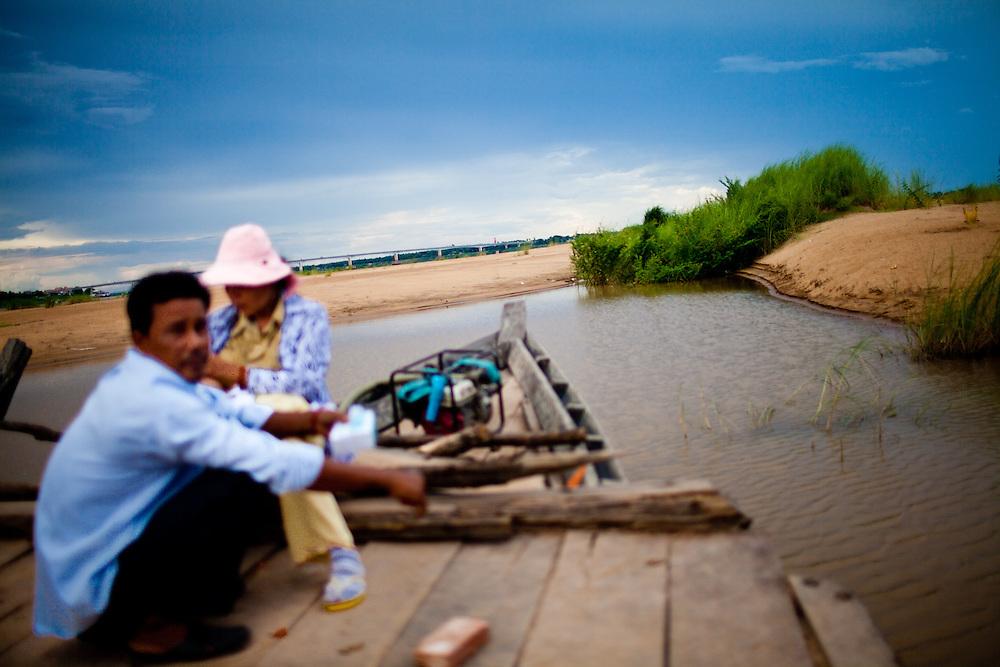 Passagiere auf einer Faehre ueber den Mekong. Im Hintergund die Insel Koh Paen in Kampong Cham, Kambodscha. 08.06.2011