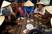 Vietnam: Hoi An. .Originally colonised by Chinese merchants, this traditional Vietnamese fishing community largely escaped damage during both the American and French Wars.Now protected by UNESCO, much of the original architecture remains in tact, providing a timeless reminder of the traditions of Vietnam...Women of the fish market relax with a game of cards (gambling is officially illegal).