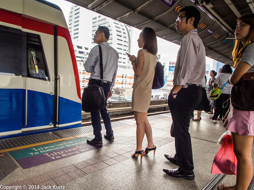 28 OCTOBER 2014 - BANGKOK, THAILAND: Passengers wait to board a Bangkok Skytrain going into Bangkok at the Saphan Taksin station. The Skytrain (called the BTS) system has a combined length of 36 kilometres and includes 34 stations, including Saphan Taksin. While there are two train tracks for most stretches of the Skytrain system, the portion on the Saphan Taksin Bridge spanning the Chao Phraya River has just one track due to limited space, causing a bottleneck when an outbound train and inbound train arrive at the bridge at the same time. The Bangkok Metropolitan Authority (BMA) had sought permission from the Department of Rural Roads to expand the Taksin Bridge in order to make way for an additional track, but the department had said it was not possible. The Saphan Taksin  station was originally supposed to be temporary and is one of the busiest on the system. It's a connecting station for the Chao Phraya River boats used by Thai commuters coming into the city from neighboring provinces and tourists who use the boats to go upriver into the old parts of Bangkok from the central business district. More than 4,000 commuters a day use the station. The BMA plans to build an elevated moving sidewalk to the river from Surasak BTS station about one kilometer away. Surasak is the nearest station to Saphan Taksin. The Skytrain system has a combined length of 36 kilometres and includes 34 stations, including Saphan Taksin.       PHOTO BY JACK KURTZ