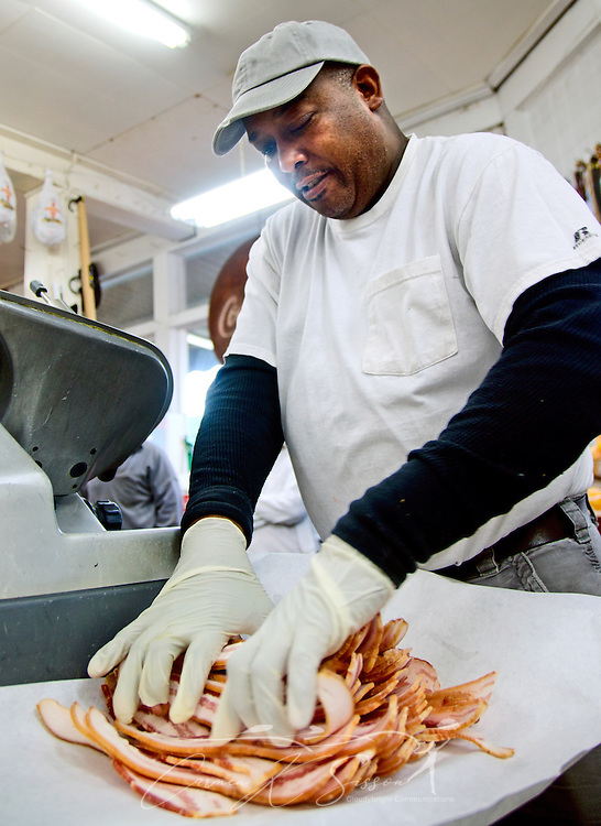 Frank Moore layers slices of bacon, preparing a package for a customer, at Williams Brothers General Store Dec. 11, 2011, in Philadelphia, Mississippi. One of the most popular features of the store is its bacon and cheese slicing station, where customers can watch their order being processed. (Photo by Carmen K. Sisson/Cloudybright)