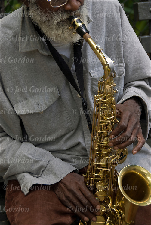 77 year old jazz musician, Giuseppi Logan, sitting on bench in Tompkins Square Park playing jazz on his saxophone.<br /> <br /> Beset with personal problems, &quot;Logan vanished from the music scene in the early '70s and for over three decades his whereabouts were unknown.&quot;<br /> <br /> &quot;My wife had me put in a mental institution,&quot; he said. &quot;She said I was an addict.&quot; He had taken drugs, anything he could get his hands on&quot;.  He was away for 30 years and everything he had. &quot;I believe if I had stayed in New York I wouldn't be poor like I am&quot;.<br /> <br /> Logan is living in New York and performing as a street musician, after years in and out of institutions.<br /> <br /> Since March 2009 he has been living at BRC, a nonprofit group for formerly homeless people over age 55, many with severe and persistent mental illness. His ailments have been identified as paranoid schizophrenia and poly substance dependence, though he no longer uses any substance regularly.<br /> <br /> In February 2010, he recorded  The Giuseppi Logan Quintet, his first album in 43 years.