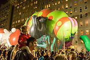 New York, NY – 27 November 2019. Thousands of spectators packed the streets around the American Museum of Natural History to see the inflation area for the balloons for Macy's Thanksgiving Day Parade. A girl rides on her father's shoulders as the Trolls look on..