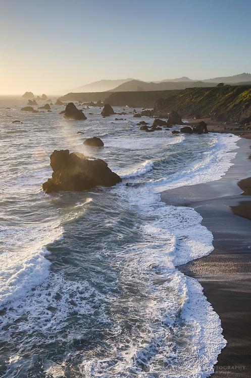 Waves crashing against sea stacks and sand beach on Sonoma Coast California