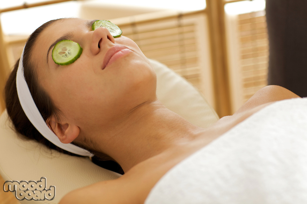 Young woman lying down in massage table with cucumbers on eyes