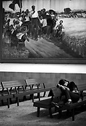 A tired tourist naps under a painting of Mao prancing though a bountiful field as she waits for a bus after a visit to Shaoshan, Mao's birthplace.
