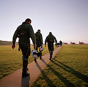 At the start of another day's work, pilots belonging to the elite 'Red Arrows', Britain's prestigious Royal Air Force aerobatic team, walk in single-file out into the pink morning light for the first winter training flight of the day at RAF Scampton, Lincolnshire. Emerging from their squadron building the aviators make their way along a pathway towards the waiting Hawk jet aircraft known the world over. Wearing winter green flying suits and carrying their helmets, their day is spent flying and de-briefing up to six times a day when weather permits. Long shadows spill over on to the airfield's cropped grass. Scampton  is one of the original World War 2 RAF stations for the Lancaster bombers the 617 Dambusters squadron who attacked the damns of the German Ruhr valley on 16th May 1943 using the Bouncing Bomb. Today, it is used almost exclusively by the team.