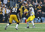 November 05, 2011: Michigan Wolverines quarterback Denard Robinson (16) passes the ball as Iowa Hawkeyes defensive lineman Broderick Binns (91) eyes him during the second quarter of the NCAA football game between the Michigan Wolverines and the Iowa Hawkeyes at Kinnick Stadium in Iowa City, Iowa on Saturday, November 5, 2011. Iowa defeated Michigan 24-16.