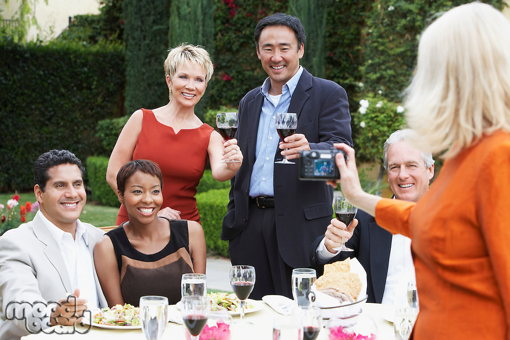 Woman photographing friends celebrating with food and drink in garden