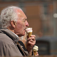 Elderly man enjoying   an ice cream on a sea side resort