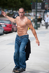 Shirtless 28 year old man in jeans on a skateboard in New York City