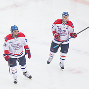 Jake Suter #28 of the UMass Lowell Riverhawks and Zack Kamrass #27 of the UMass Lowell Riverhawks in action during the Frozen Fenway game between The Northeastern Huskies and The UMass Lowell Riverhawks at Fenway Park on January 11, 2014 in Boston, Massachusetts.
